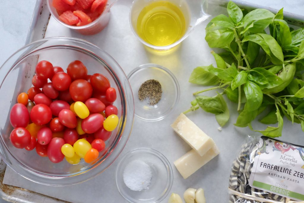 Baking sheet with cherry tomatoes basil pasta parmesan olive oil