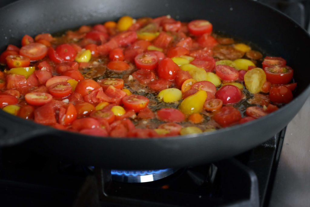 cherry tomatoes sauteing in a black skillet