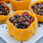 Orange bell peppers stuffed with black rice and vegetables on a white plate