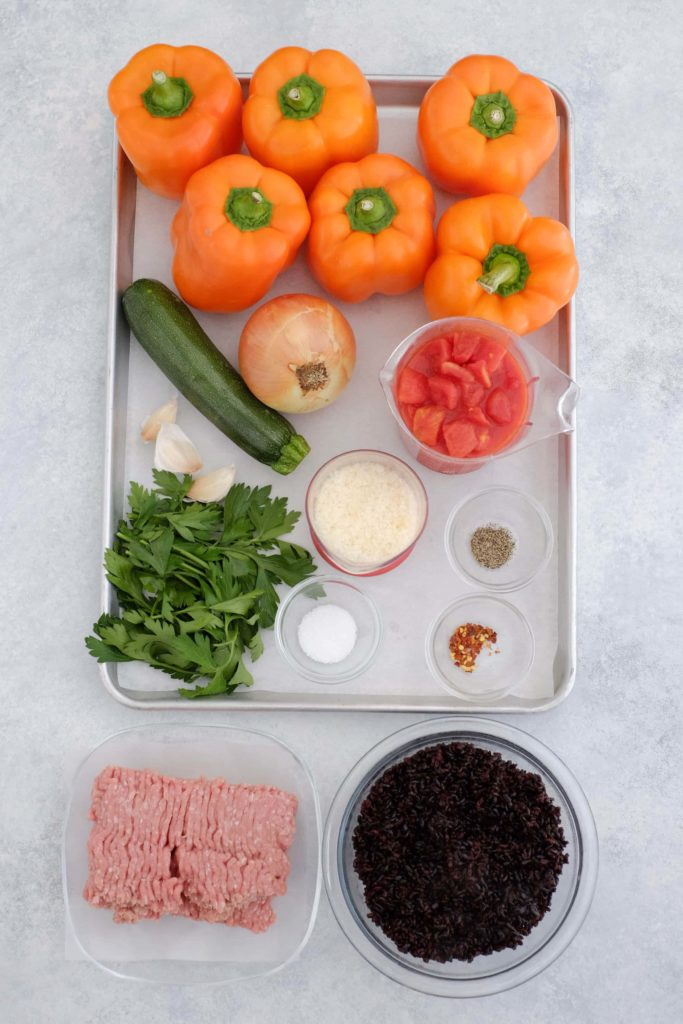 Baking sheet with orange peppers zucchini italian parsley tomatoes ground chicken garlic