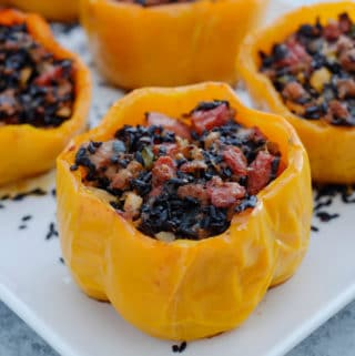 Stuffed yellow bell peppers sitting on white plate