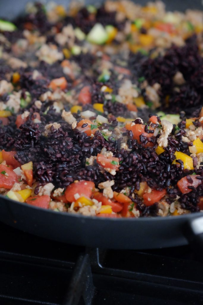 Black rice ground turkey and vegetable cooking on the stove in a pan