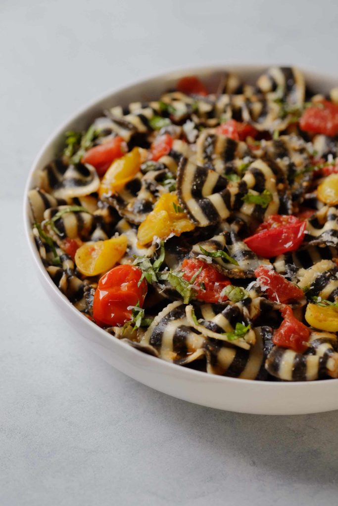 Black and white pasta with cherry tomato and basil sauce in white bowl