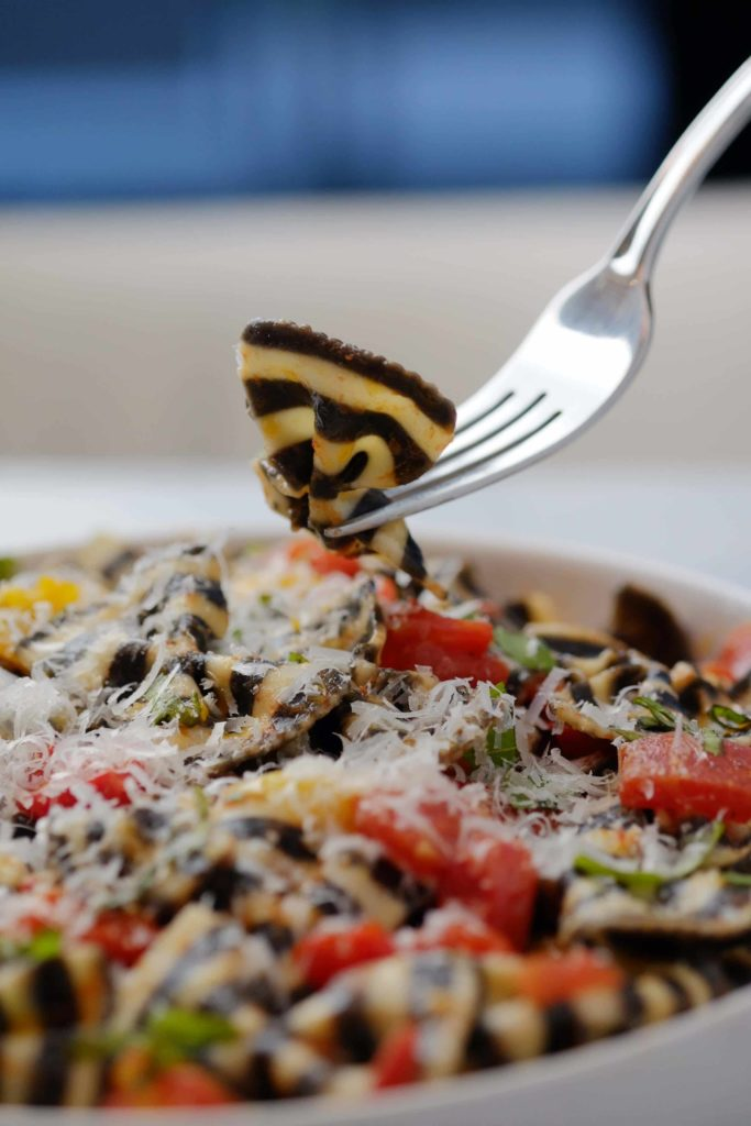 black and white pasta with cherry tomato basil sauce on fork