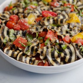 black and white pasta with cherry tomato basil sauce in white bowl