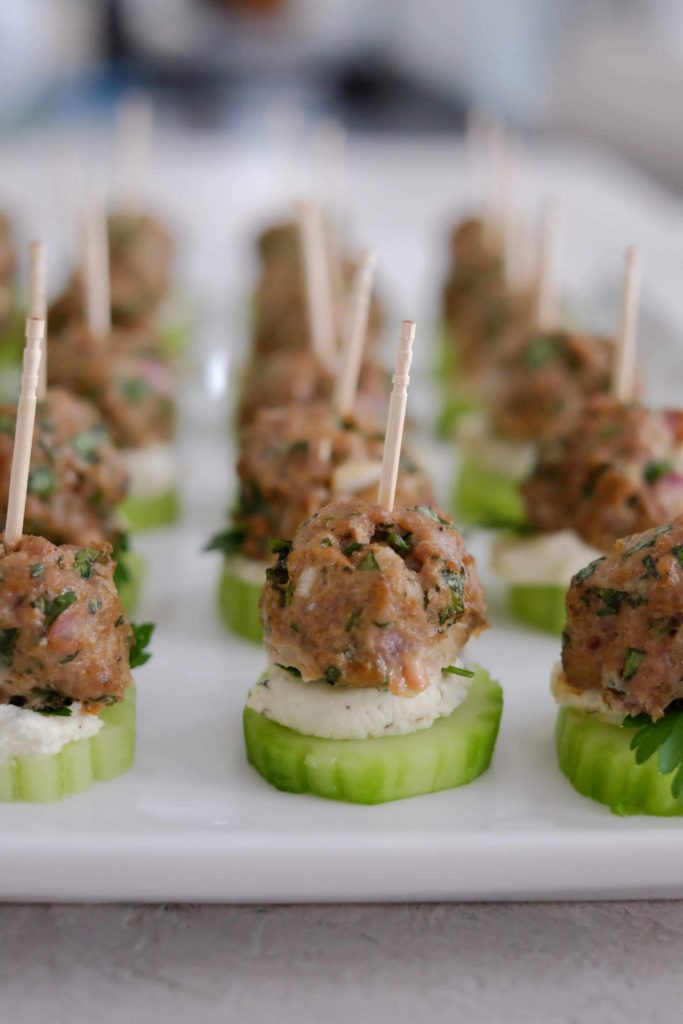 Lamb meatballs on a cucumber on a white plate