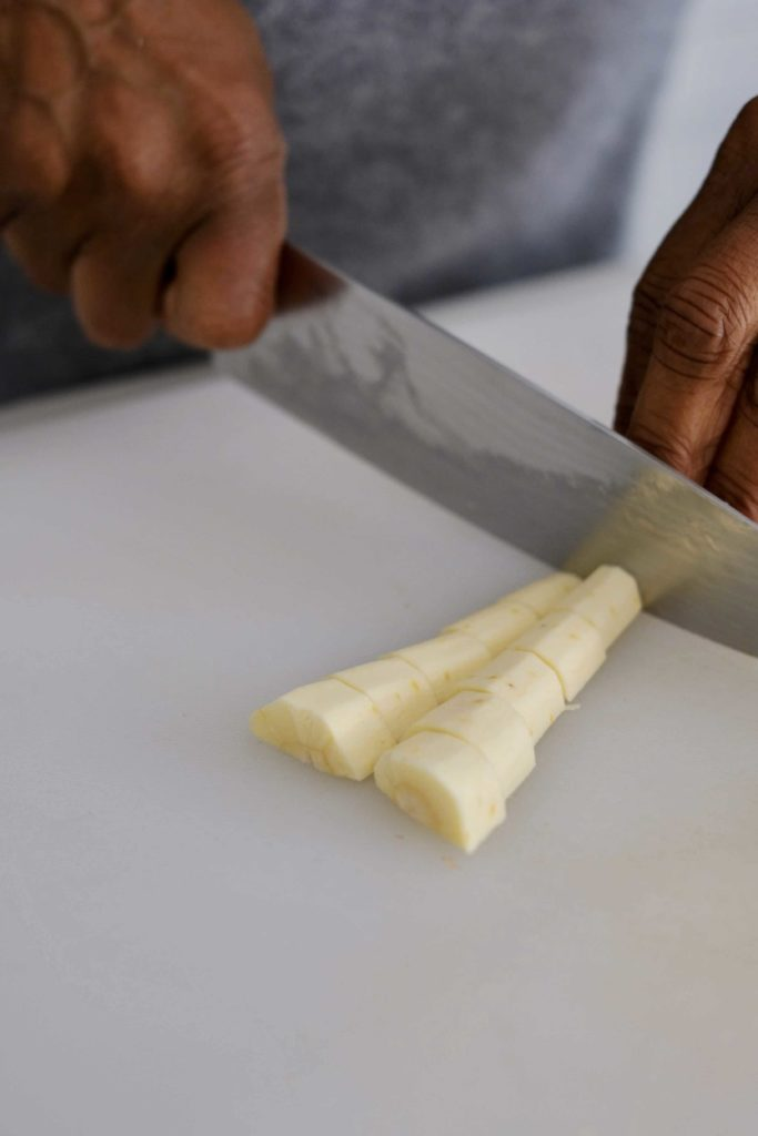 Parsnips being sliced with a knife on a white cutting board