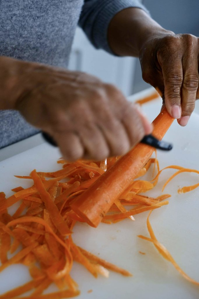 Carrots being peeled by hand over a white cutting board