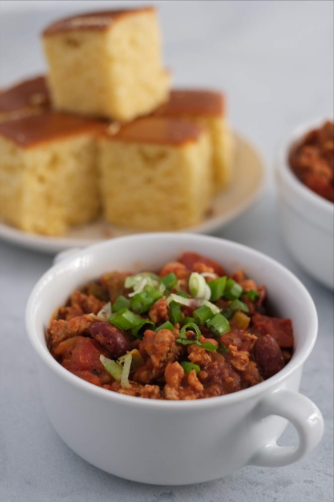 Turkey chili with green onions on top in a white bowl and corn bread on a plate