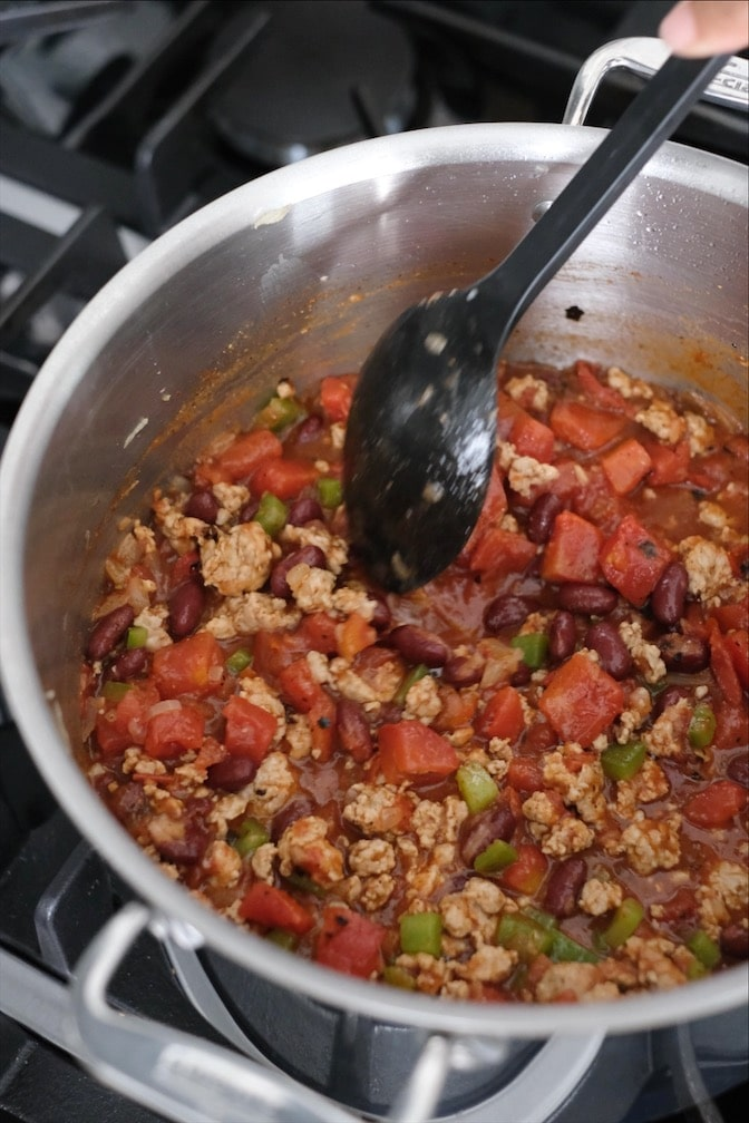 Turkey chili being stirred in a large pot while cooking on a stovetop.