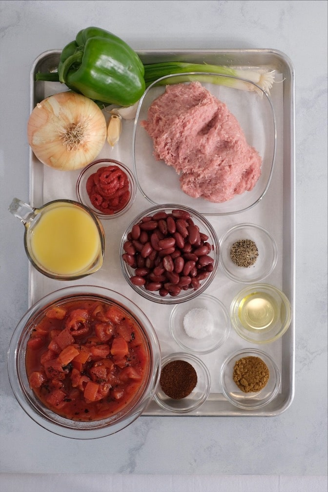 Sheet pan with raw ground turkey onion tomatoes green bell pepper garlic olive oil and spices on it.