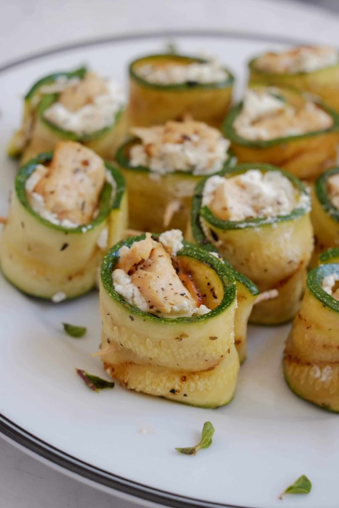 Grilled zucchini, chicken and goat cheese roll-ups on a white plate.
