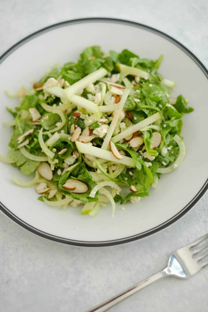 Arugula apple and fennel salad on a black and white plate