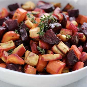 Roasted beets carrot parsnips with thyme in a white bowl.