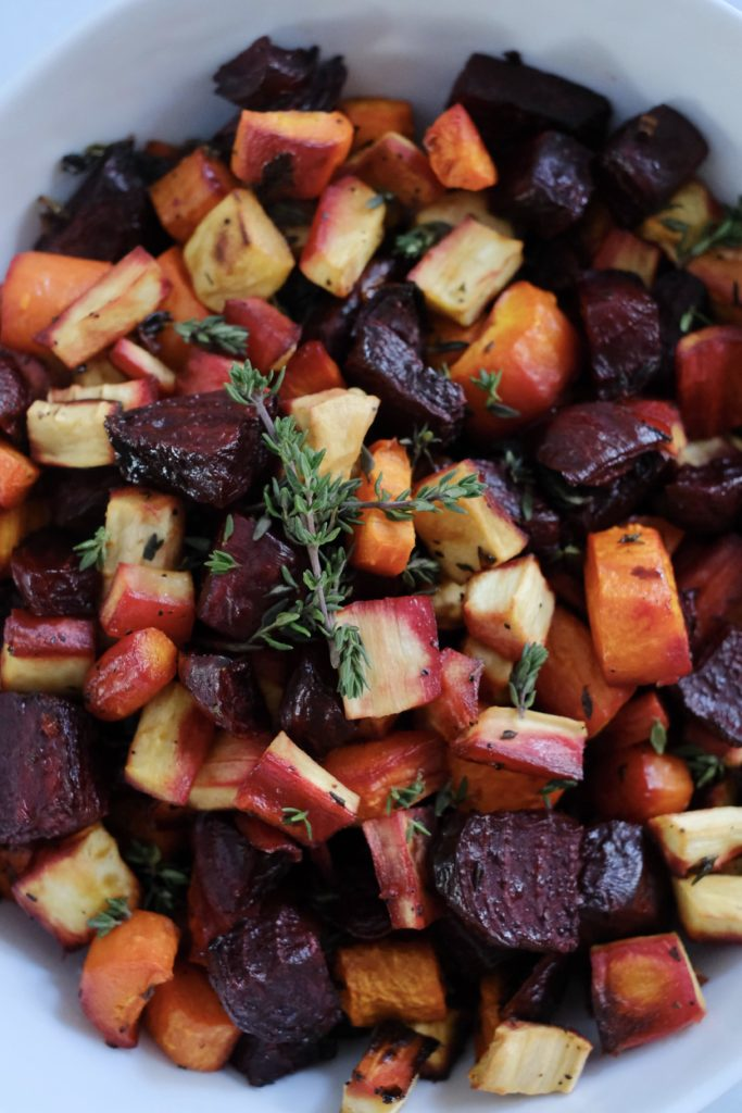 Close up of roasted beets carrot parsnips with thyme.