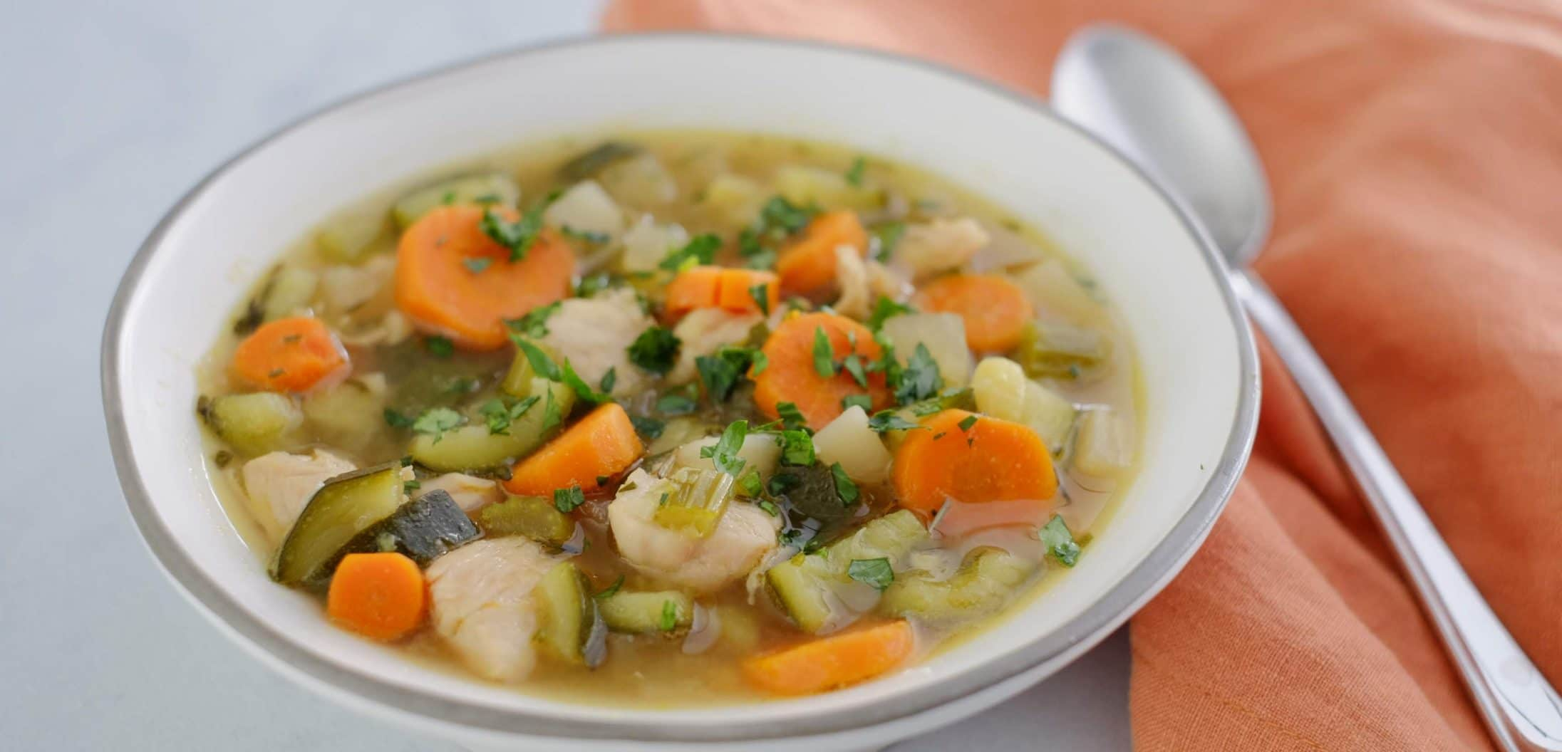 chicken vegetable soup in white bowl with orange napkin and spoon
