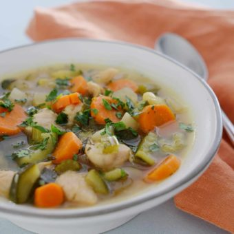 chicken vegetable soup in a white bowl with orange napkin and spoon