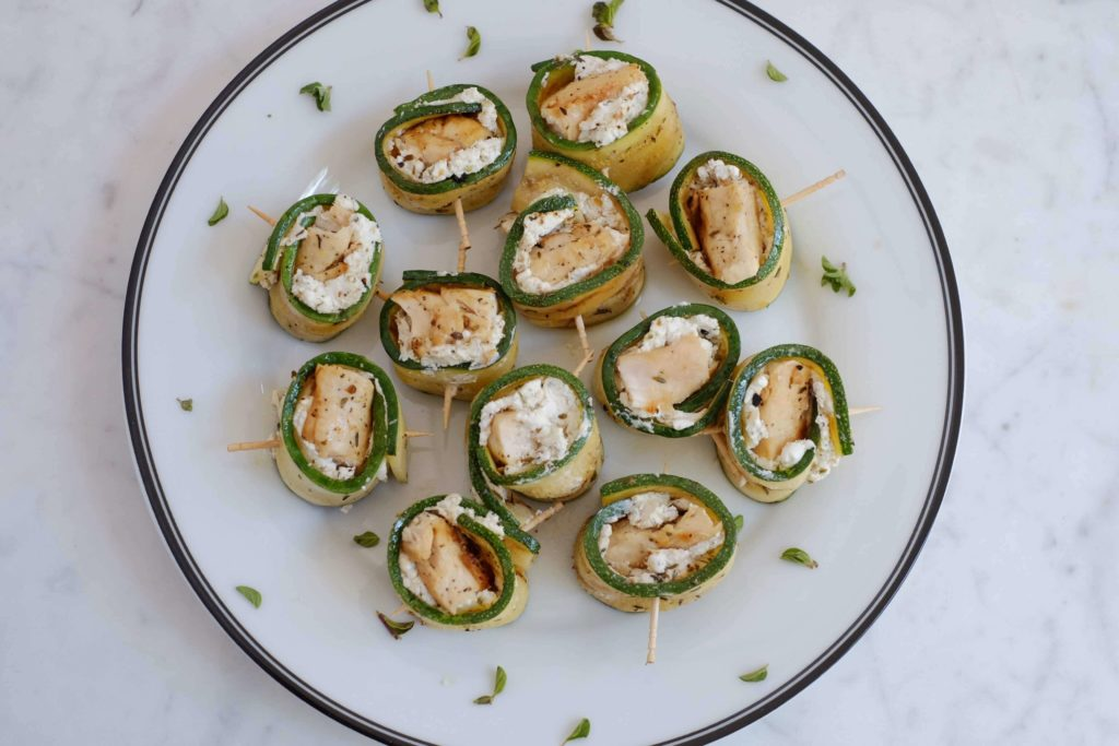 Grilled zucchini, chicken and goat cheese roll-ups on a white plate with a black rim.