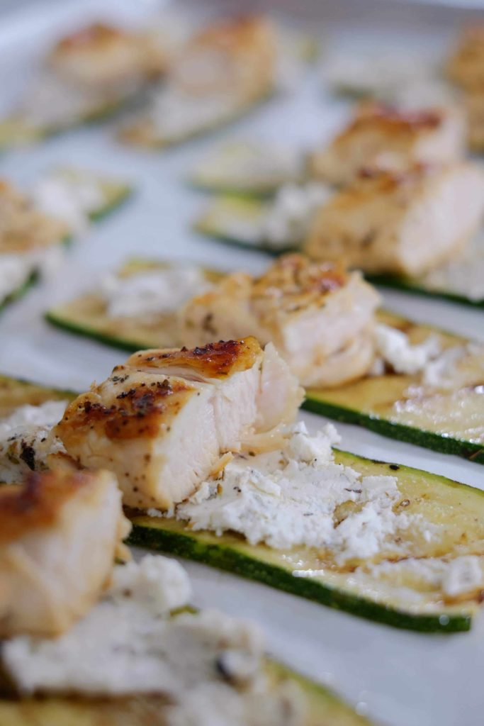 Grilled chicken and goat cheese spread on a slice of grilled zucchini.