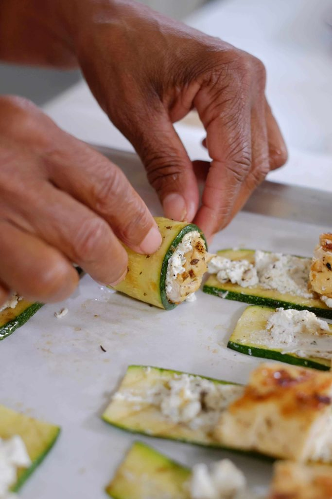 Grilled chicken and goat cheese spread on a slice of grilled zucchini being rolled up.