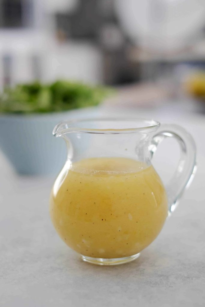 Honey apple cider vinaigrette in a small glass pitcher