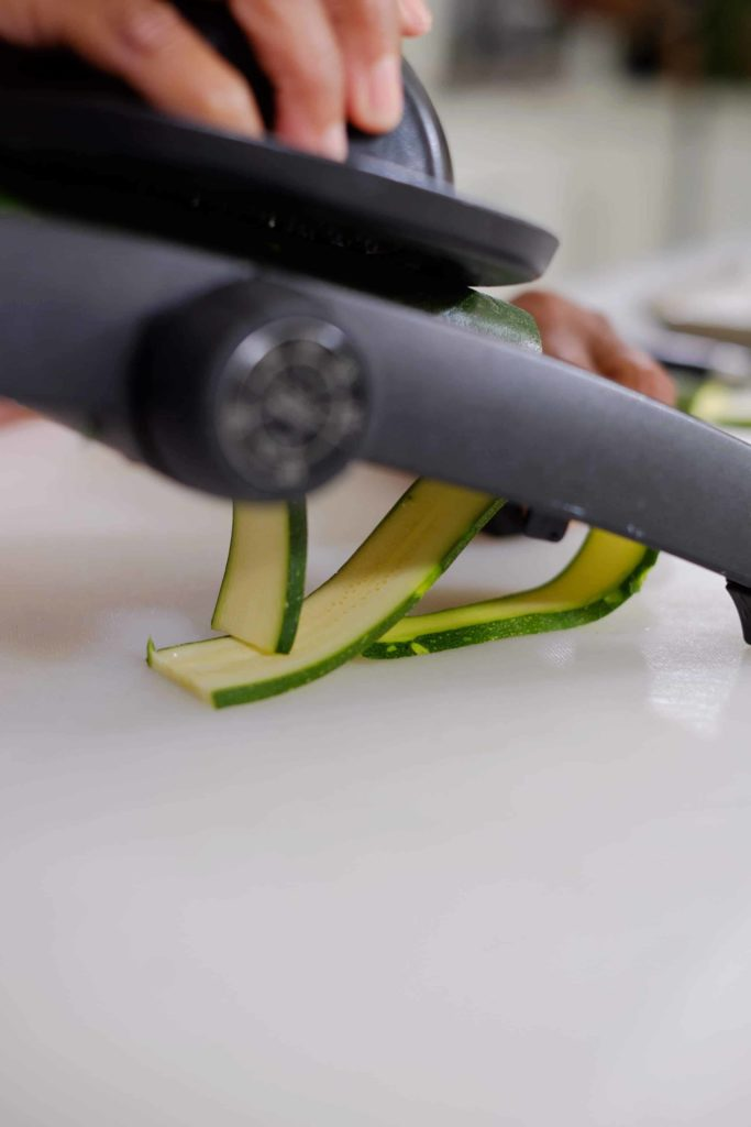 A person's hands showing how to slice zucchini on a mandoline.