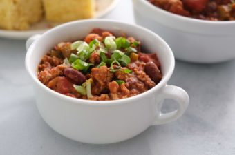 Turkey chili with green onions on top in a white bowl and cornbread on a white plate.