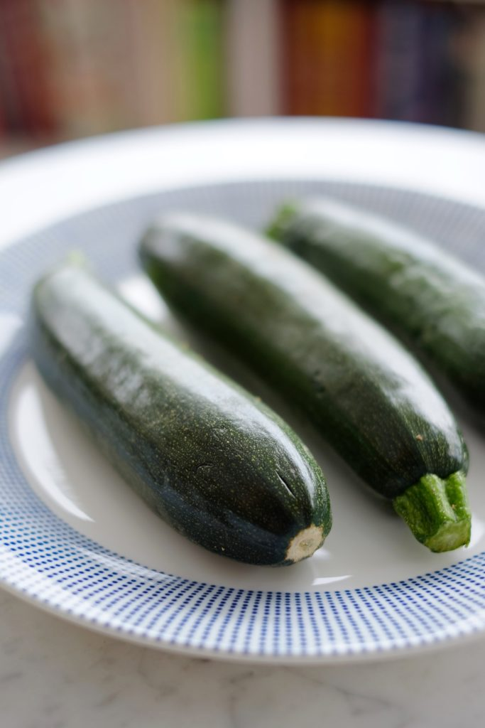 Three fresh whole zucchini sitting on a blue and white plate.