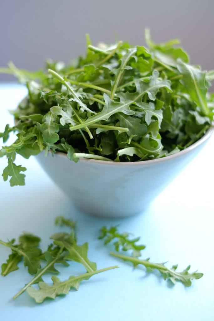Fresh arugula in light blue bowl sitting of write counter