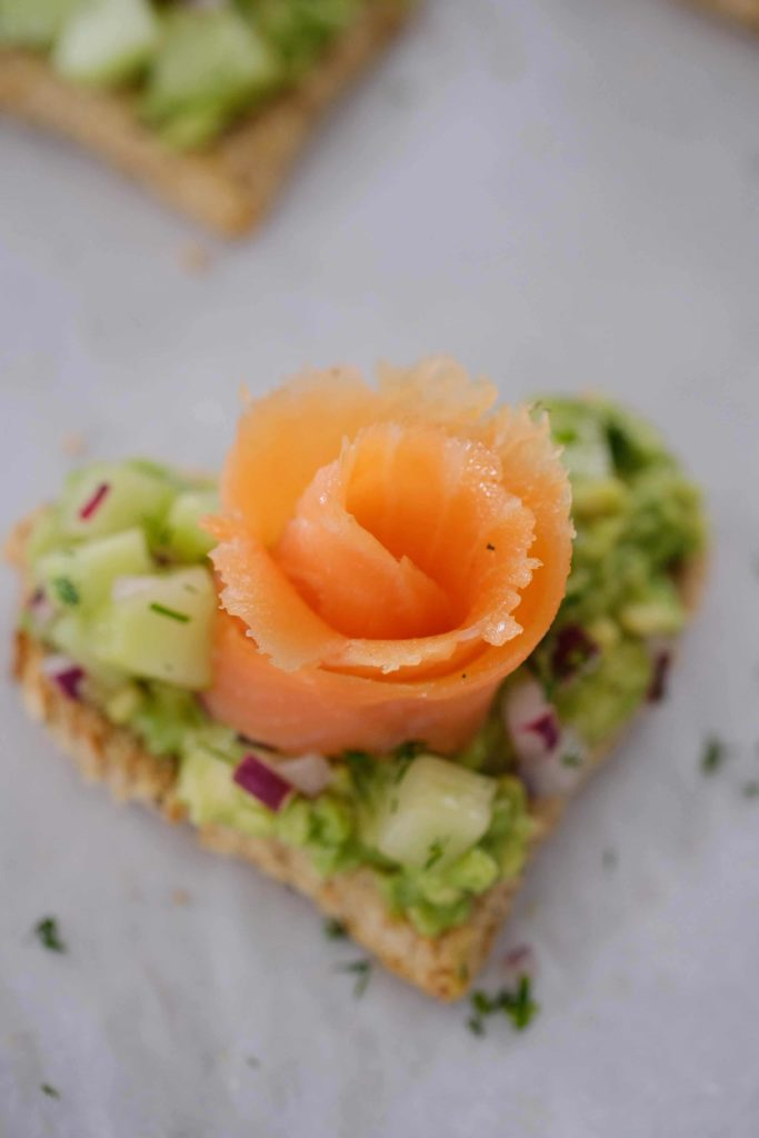 A heart shaped avocado toast with a smoked salmon rose sitting on white parchment paper
