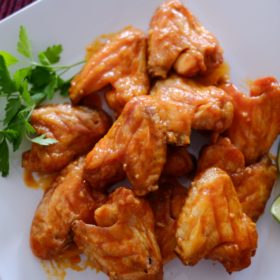 Baked buffalo chicken wings on a white platter with two limes and parsley