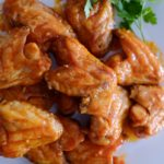 Baked buffalo chicken wings on a white plate with two lime wedges and sprigs of parsley