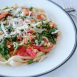 Brown rice pasta with arugula tomatoes sitting on a whit plate with black rim