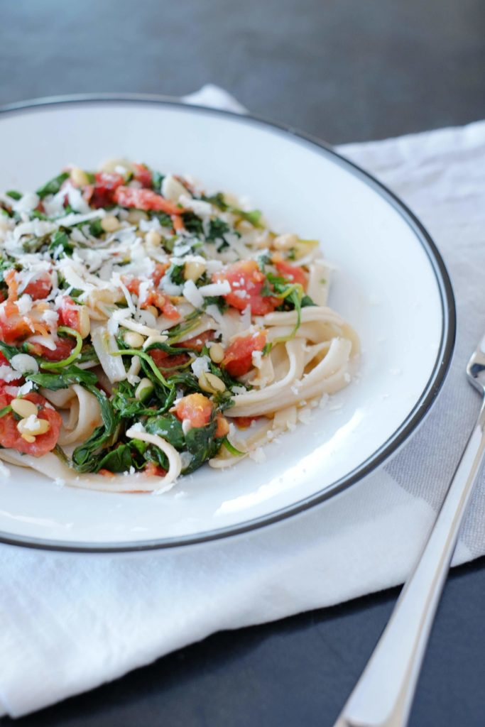 Brown rice pasta with arugula and tomatoes on a white plate with black rim