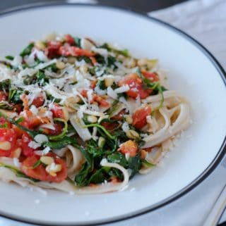 Brown rice pasta with tomatoes and arugula on a white plate sitting on a white napkin with a fork