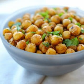 A light blue bowl filled with roasted chickpeas sitting on a folded napkin