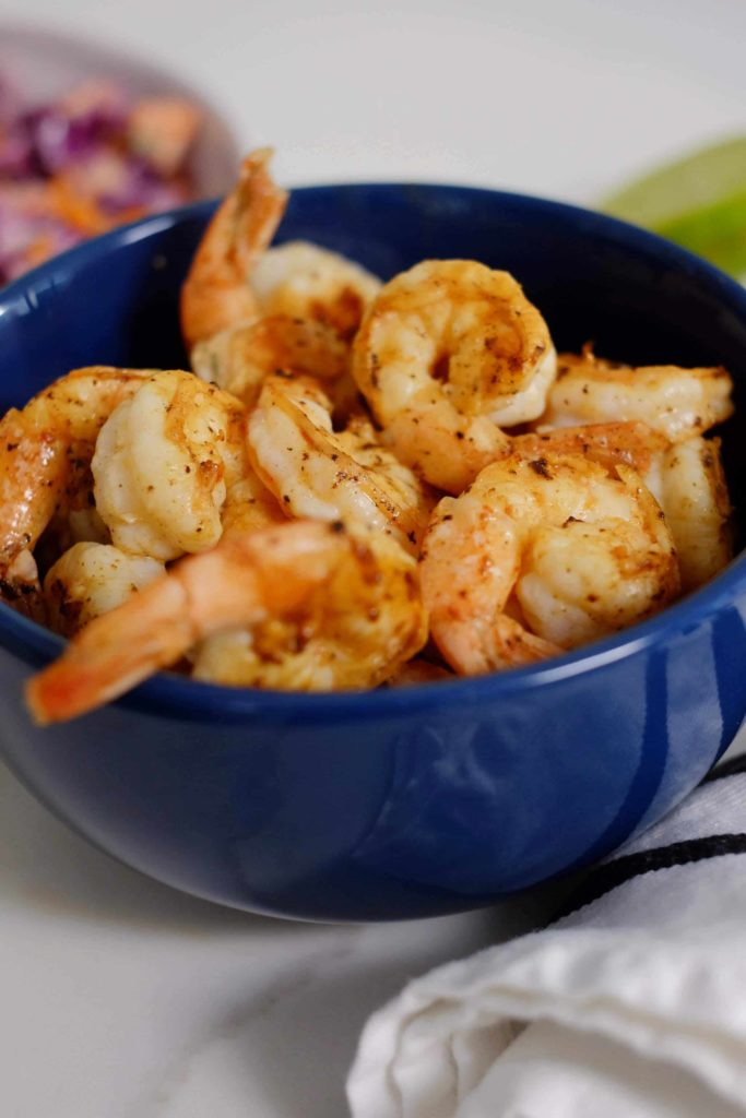 A blue bowl filled with grilled shrimp.
