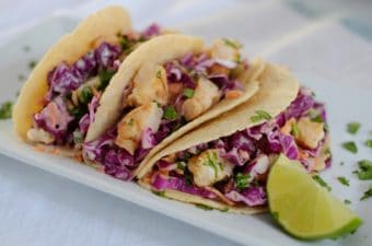 Three grilled shrimp tacos with purple cabbage slaw on a white plate with a lime wedge