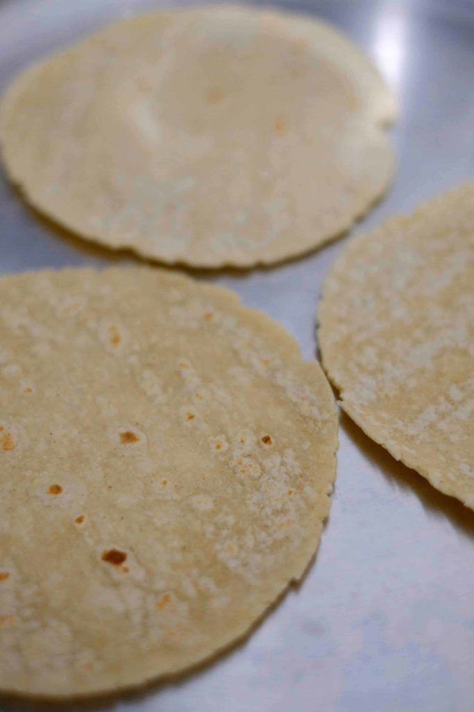 A pan with three corn tortilla warming in a pan.