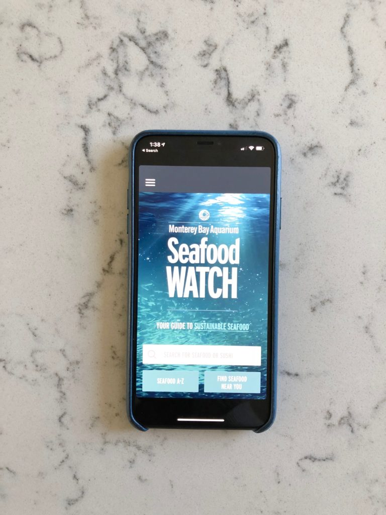 iphone with seafood watch app on screen on marble