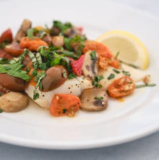 Baked cod with tomatoes and mushrooms on a white plate