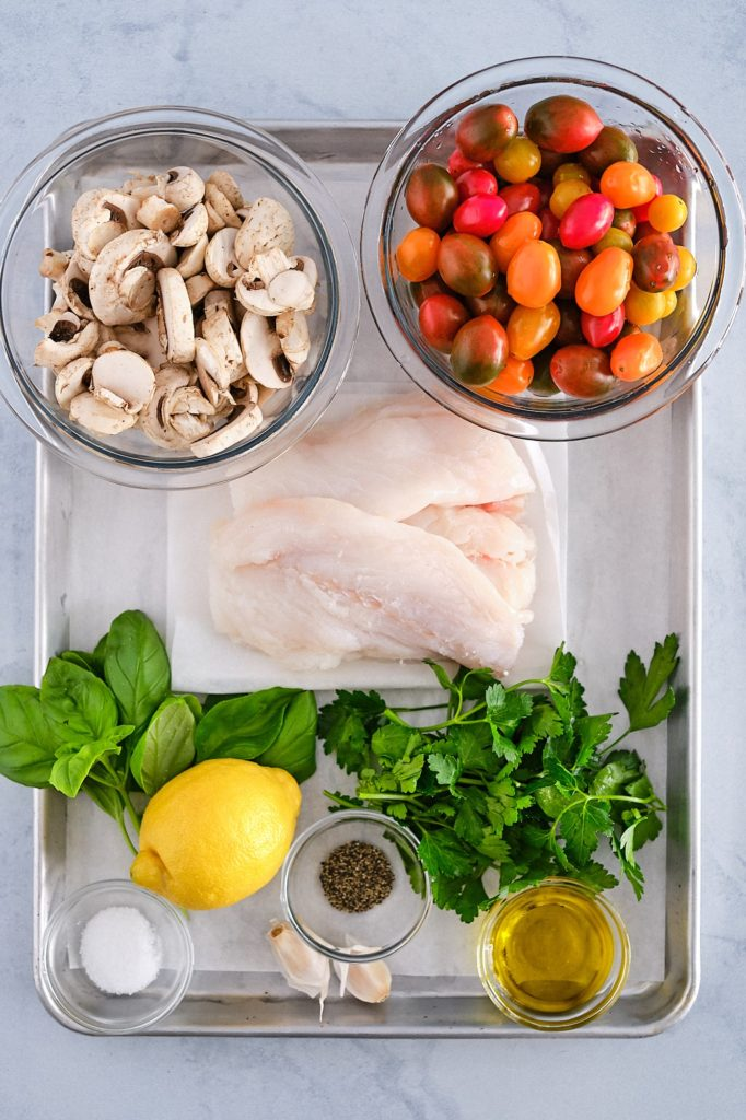 Fresh cod, italian parsley, basil, olive oil, garlic, salt, pepper and a lemon on a baking sheet