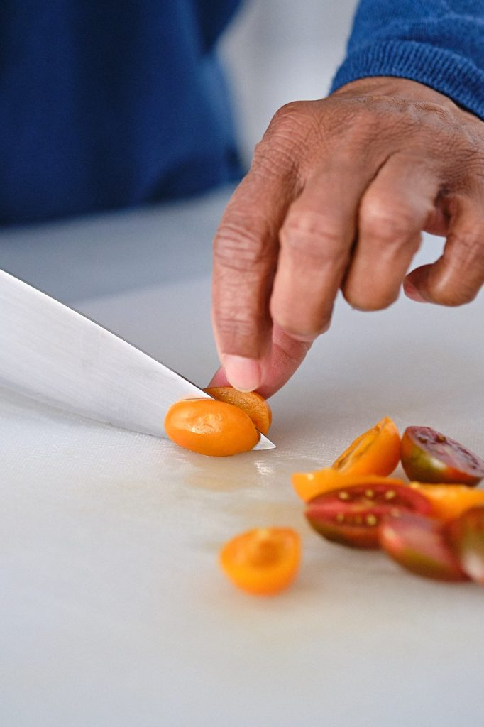 slicing cherry tomatoes in half with a knife