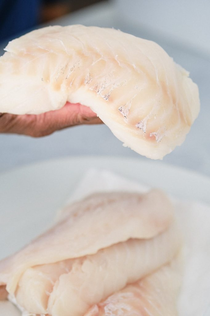 cod fillet in hand with two cod fillets on a white plate