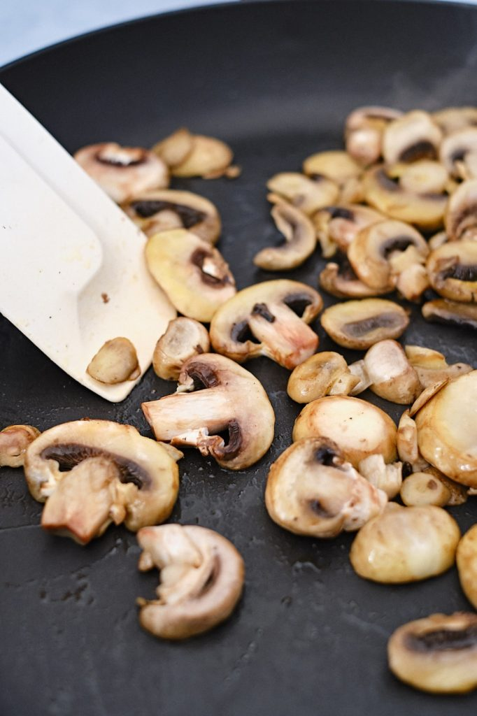 Mushrooms being sauteed in a non-stick black skillet