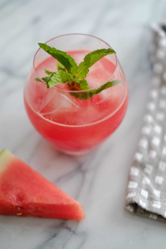 watermelon cocktail in a glass with mint on a marble counter with a wedge of watermelon
