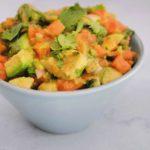 Papaya avocado salad in a blue bowl on a marble countertop