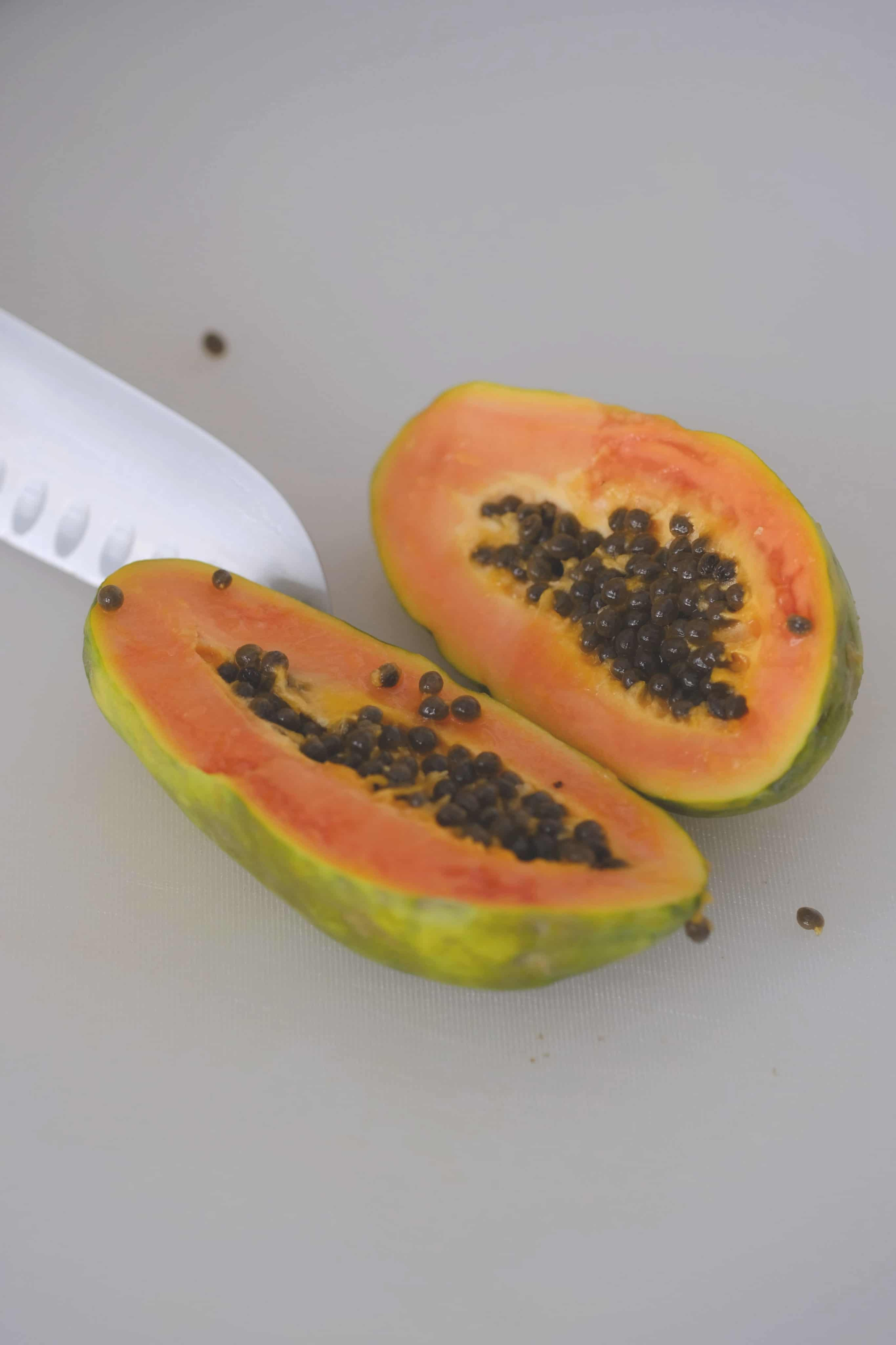 a halved papaya on a white cutting board with a knife
