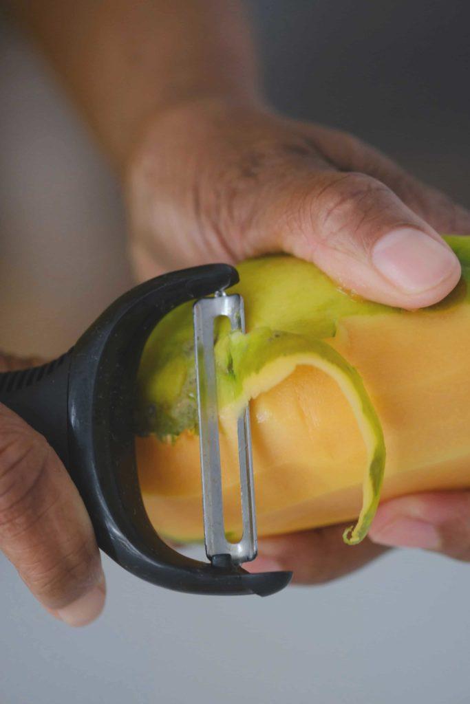 papaya being peeled with a peeler