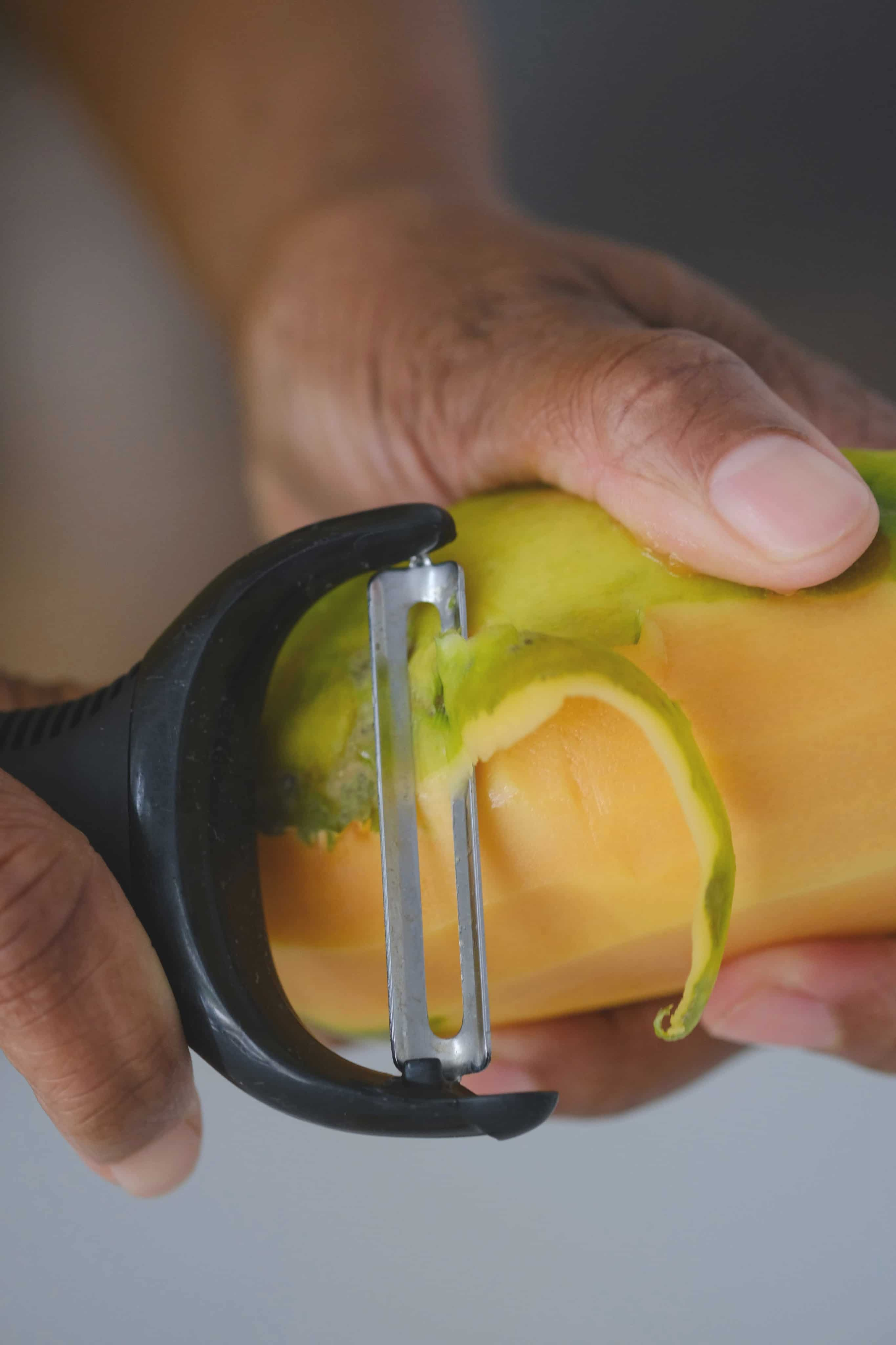 papaya being peeled with a peeler